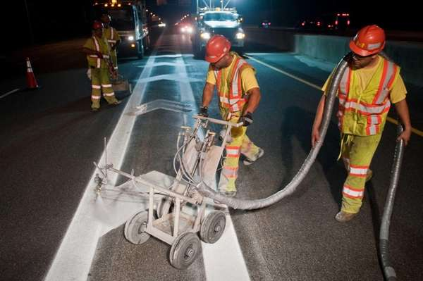 Abner Vega, left, controls a paint cart while