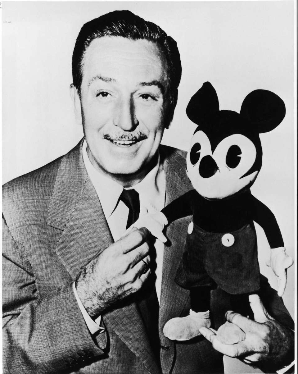 Walt Disney poses with one of the first