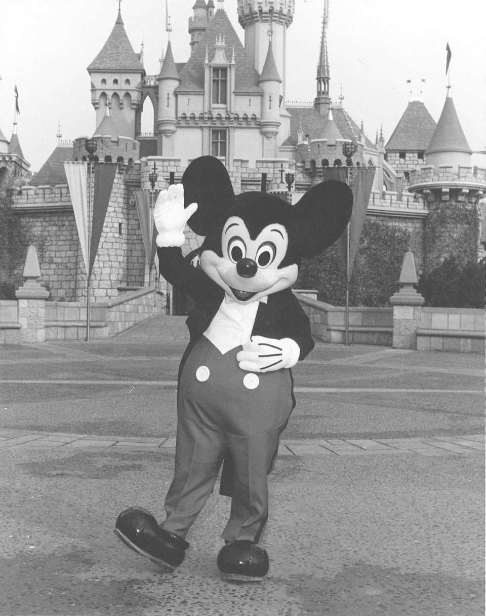 Mickey Mouse waves in front of Disneyland in