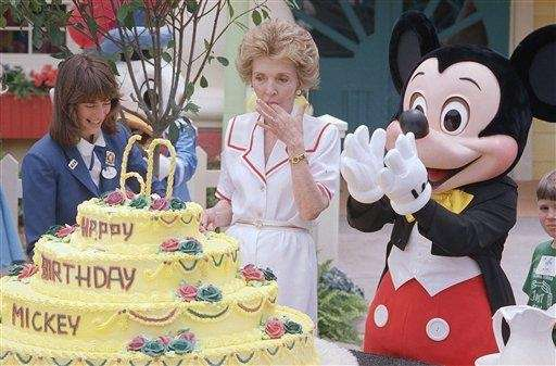 First lady Nancy Reagan helps Mickey Mouse cut