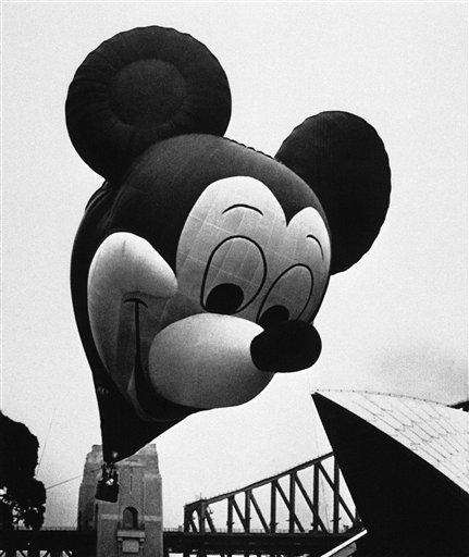 A Mickey Mouse balloon soars over two of