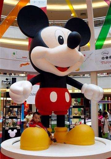 A boy sits below a giant Mickey Mouse