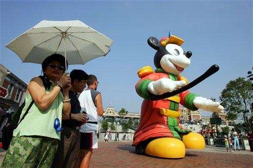 Visitors watch a giant Mickey Mouse on parade