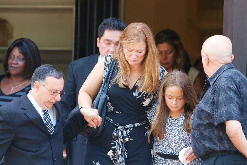 Mourners leave the church after the funeral for