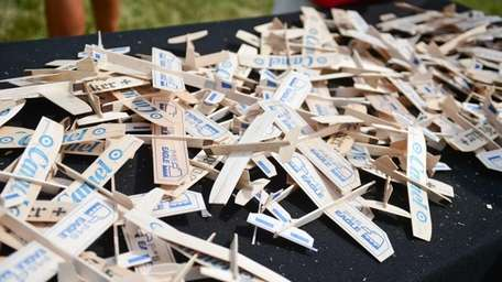 Wooden airplanes are displayed on a table during