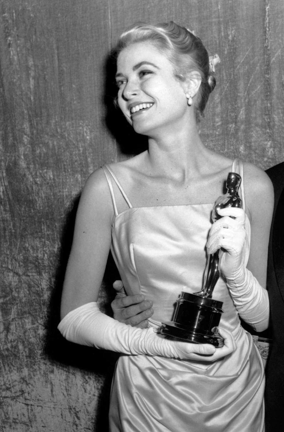 Actor Grace Kelly, posing with her Oscar statuette