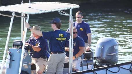 An FBI dive team leaves with supplies to