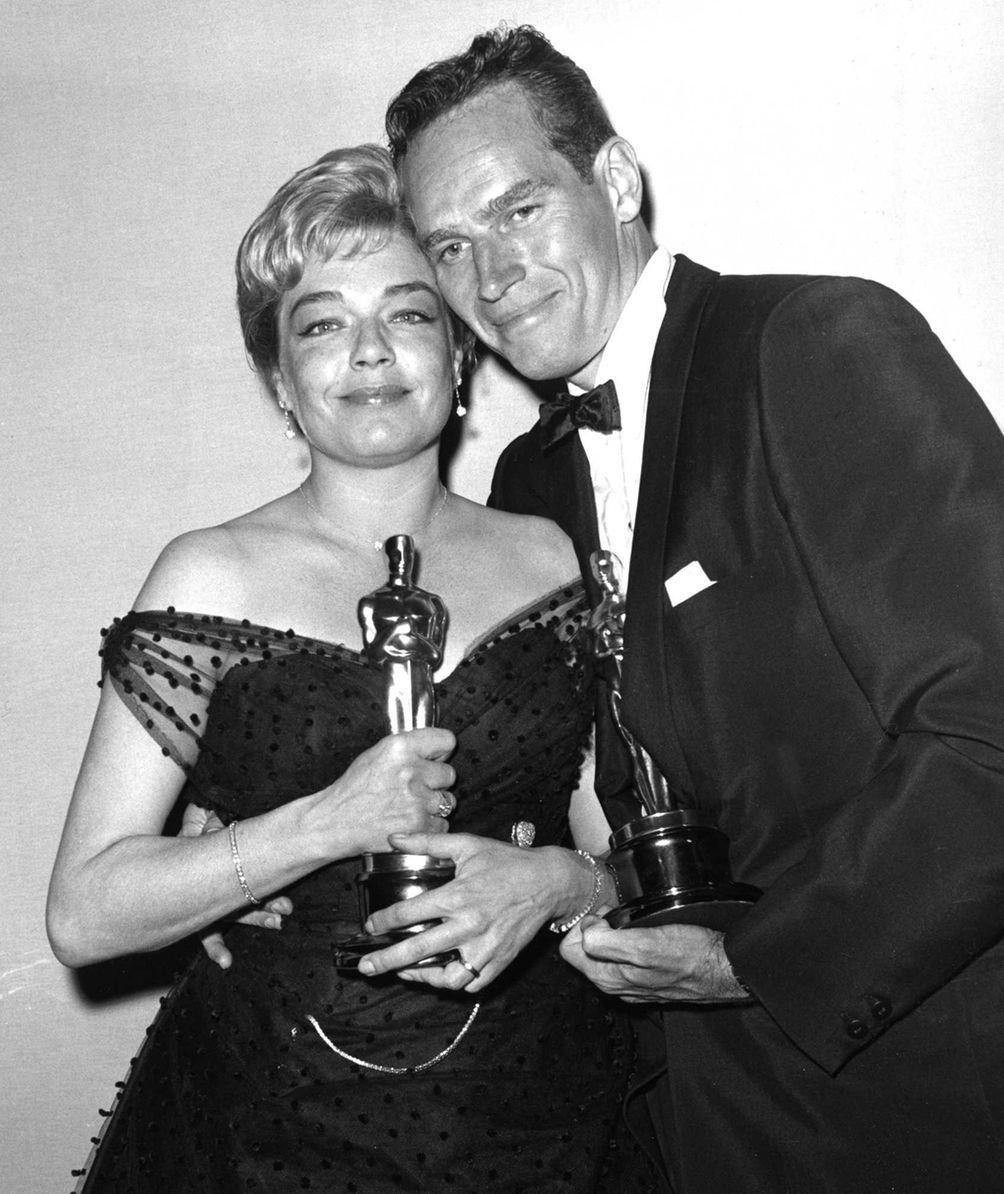 Actors Simone Signoret and Charlton Heston, posing with