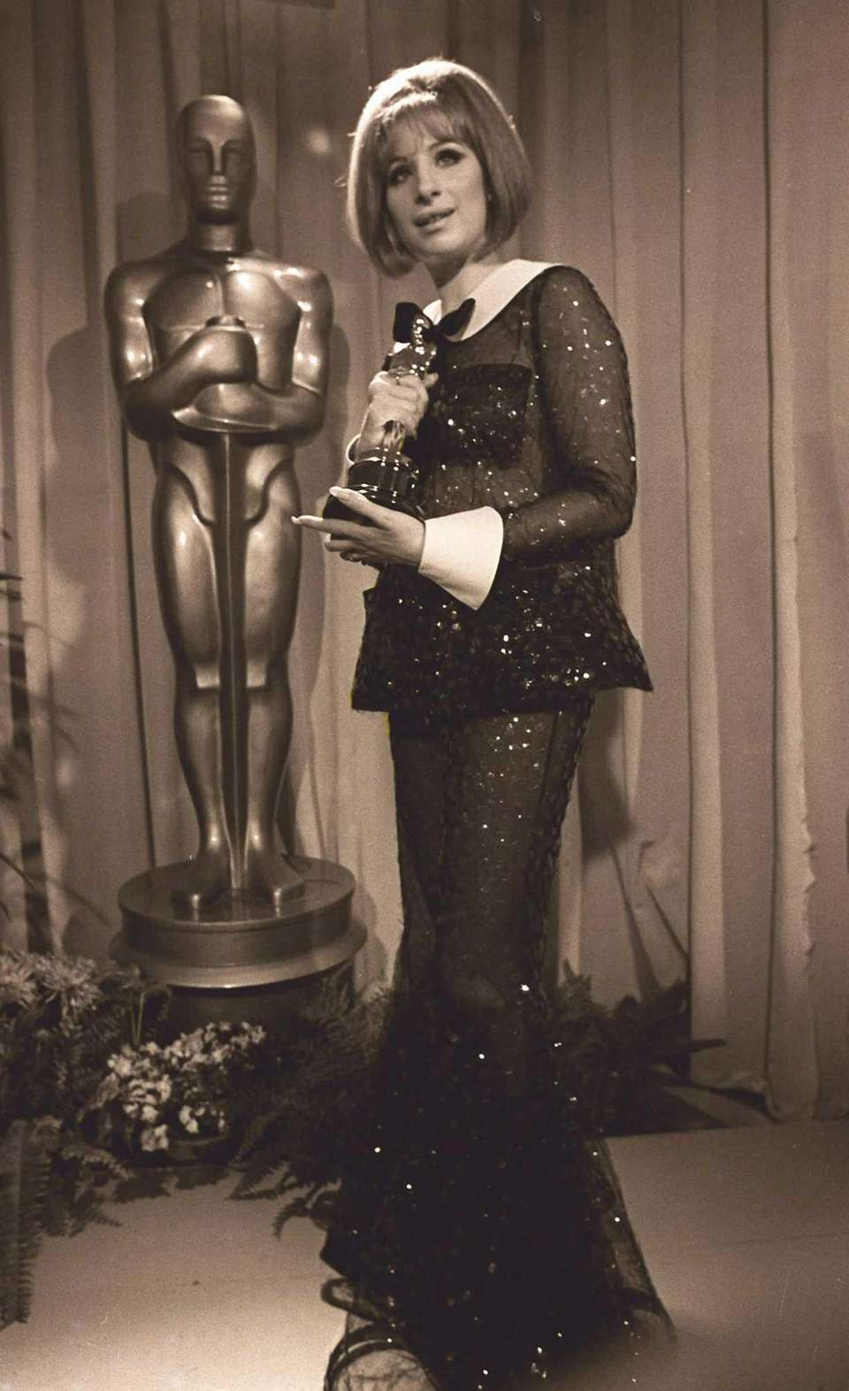 Barbra Streisand, holding the Oscar statuette she won