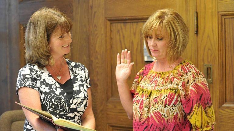 Kings Park School District clerk Patti Capobianco, left,
