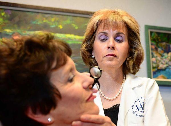 Dr. Pamela Basuk, dermatologist, examines a patient in