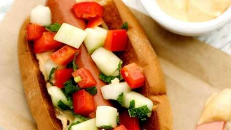 A hot dog topped with cucumber salsa and
