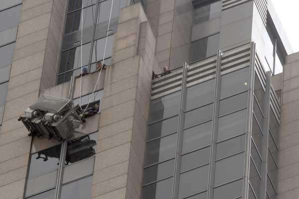 Firefighters rescue workers hanging on a scaffold in