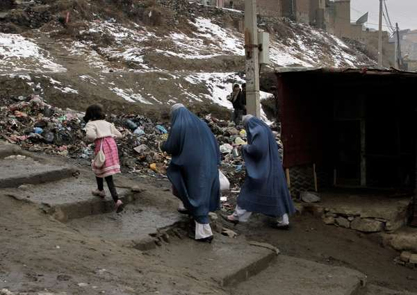 Afghan women walk to their homes in Kabul,