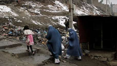 Afghan women walk to their homes in Kabul,
