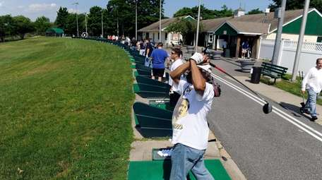 Golf enthusiasts practice their swing at the driving