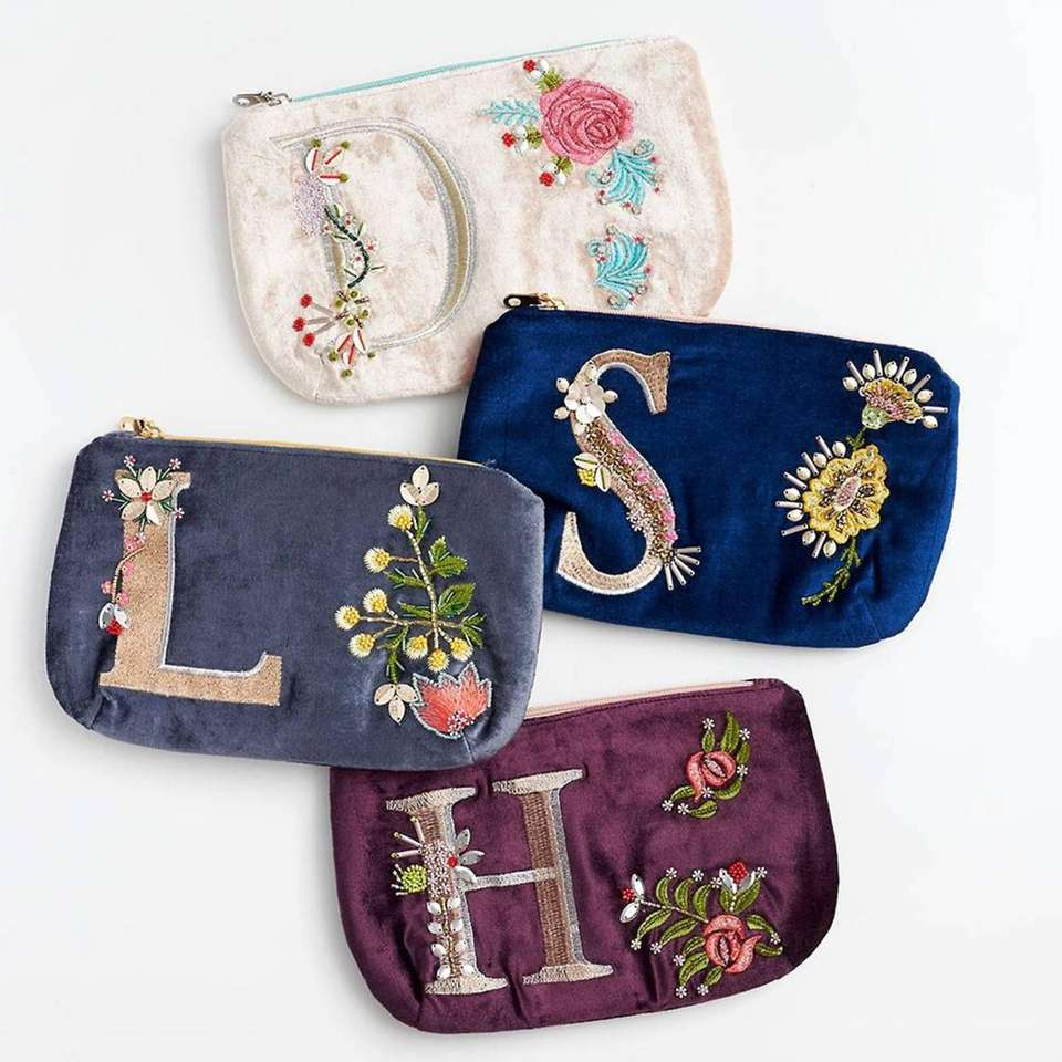 This hand-stitched velvet pouch features an initial letter,