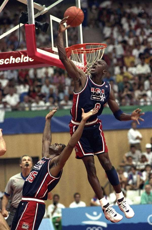 USA's Michael Jordan sails high above teammate Magic