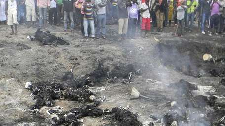 People look at charred bodies following fuel tanker