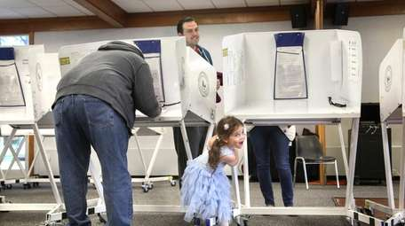 Paige Lawrence, 4, plays under voting booths while