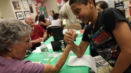 Volunteer Judie Horowitz enjoys friendly arm wrestling with
