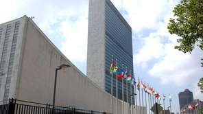 Pedestrians walk by the United Nations headquarters building.