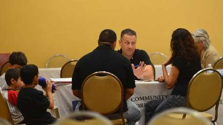 A housing counselor meets with homeowners during a