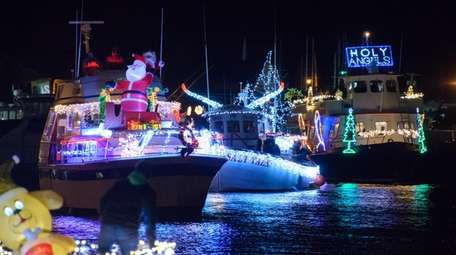 Watch from the shoreline as illuminated boats make