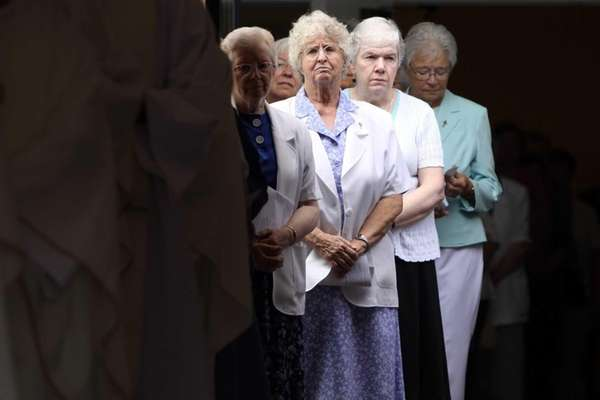 Mourners look on as Sister Jacqueline Walsh's casket