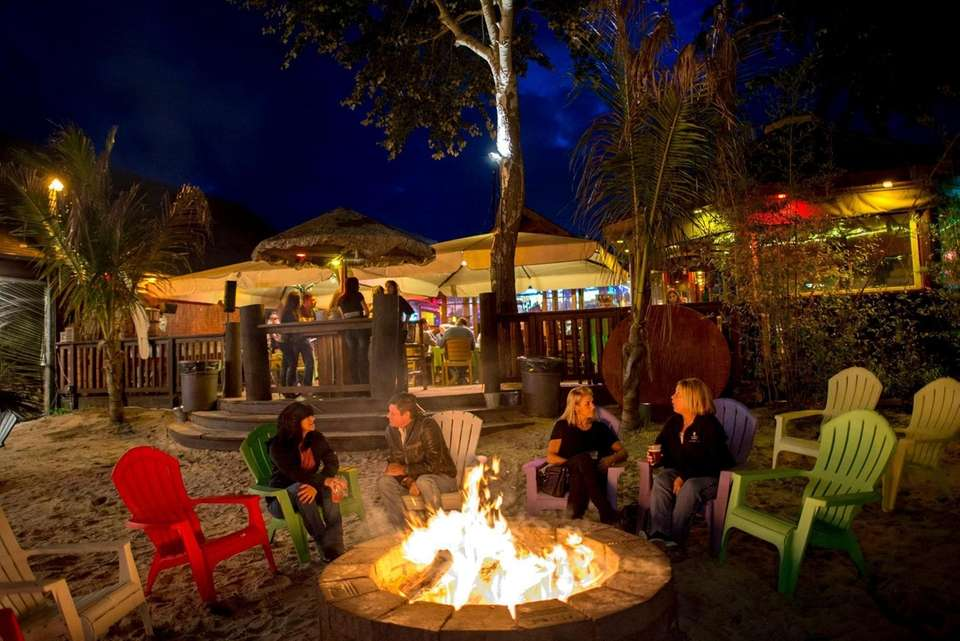 Patrons sit by the outdoor fire pit at