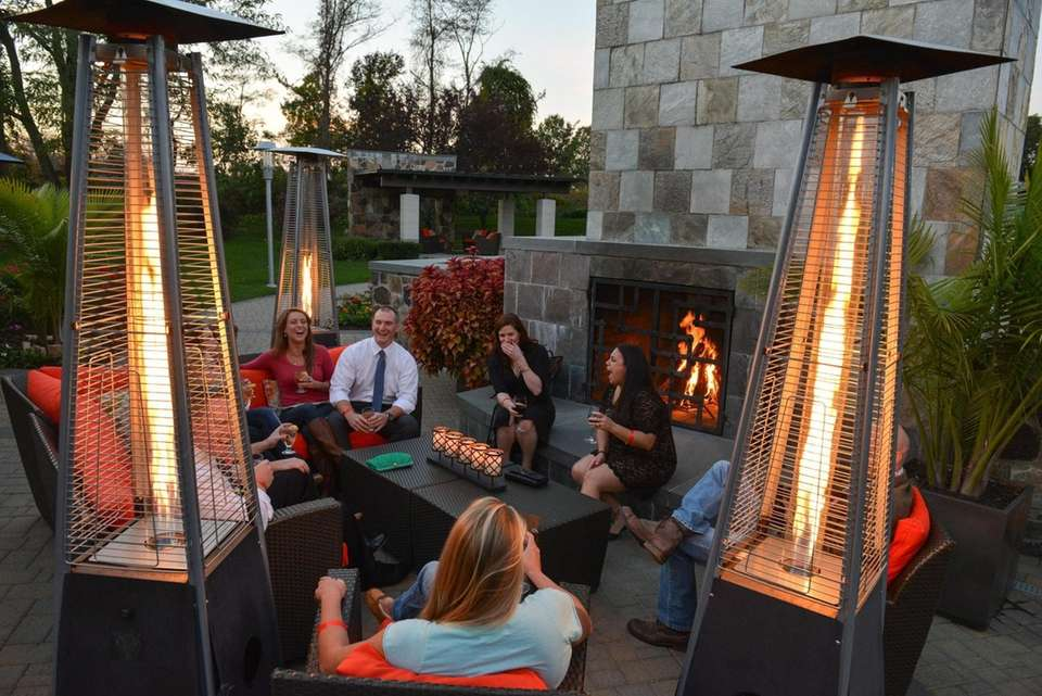 Guests socialize around the outdoor fireplace and triangular
