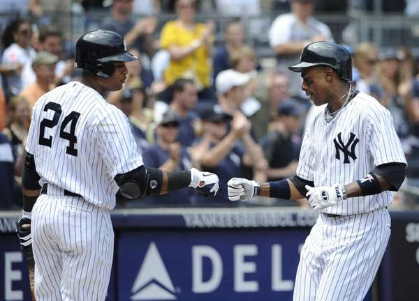 Robinson Cano, left, greets Curtis Granderson after Granderson
