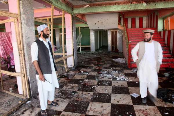 Afghan men inspect a damaged wedding hall that