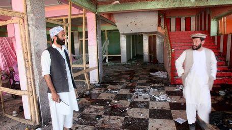 Afghan men inspect a damaged wedding hall that