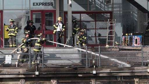 Firefighters work to extinguish a fire at Pier