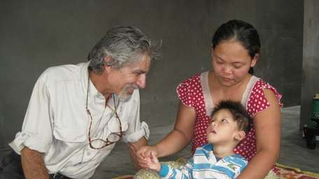 Joe Sciacca visits a young boy in Hue,