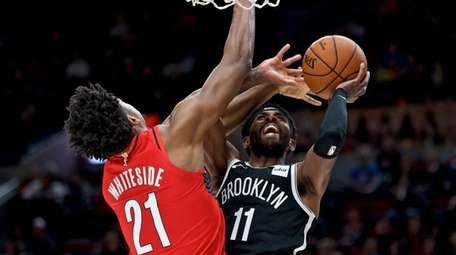 Nets guard Kyrie Irving, right, shoots over Portland