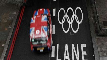 A taxi cab drives past an Olympic lane