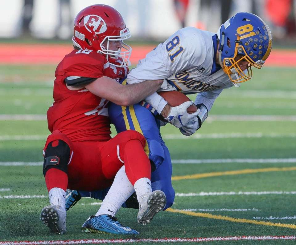 Comsewogue's Anthony Cambria (81) gets taken down by