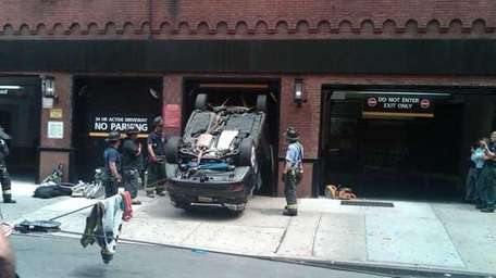 FDNY firefighters remove a car that fell 5