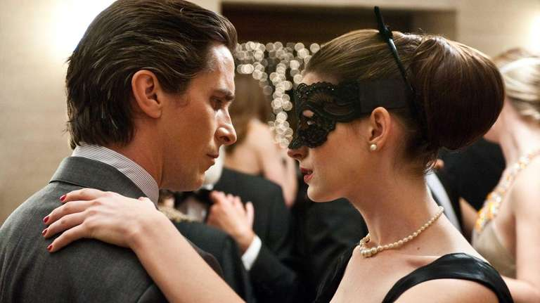 Christian Bale as Bruce Wayne and Anne Hathaway