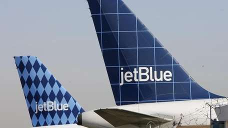 JetBlue aircraft sit on a Kennedy Airport tarmac.