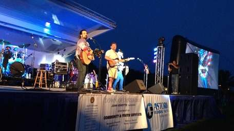 Country band SixGun performs underneath colored lights at
