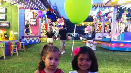 Four-year-olds Keisy Perichi, left, and Allison Tores hold