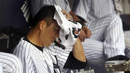 Hiroki Kuroda wipes sweat off his face during
