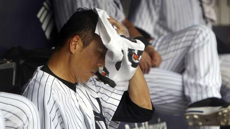 Hiroki Kuroda wipes sweat off his face during