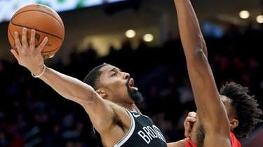 Nets guard Spencer Dinwiddie, left, shoots as Portland