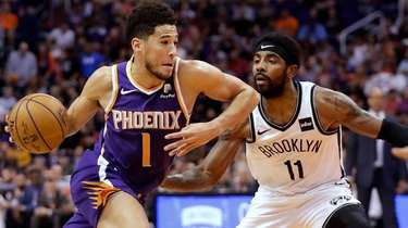 Phoenix Suns guard Devin Booker drives past Nets