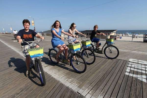 Friends ride together along the boardwalk in Long
