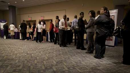 Job seekers wait in line to talk to
